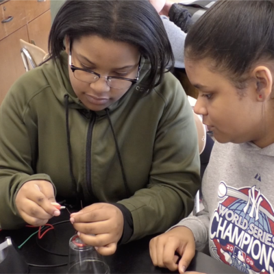 "Two female middle school students work on building a homemade audio speaker for the OpenSciEd ""Sound"" unit."
