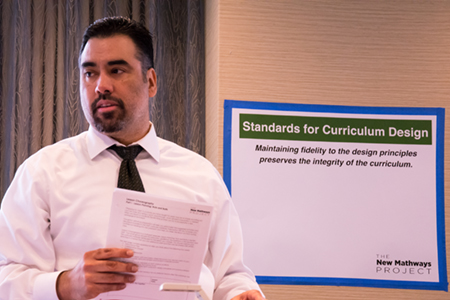 """A Latinx man in his early 40s stands, speaking to workshop attendees. Visible on the wall behind him is a poster reading """"Standards for Curriculum Design"""""""