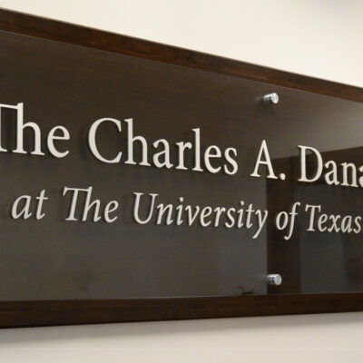 "A large wooden sign reading ""The Charles A. Dana Center at The University of Texas at Austin"" hangs on a wall in the Dana Center office."