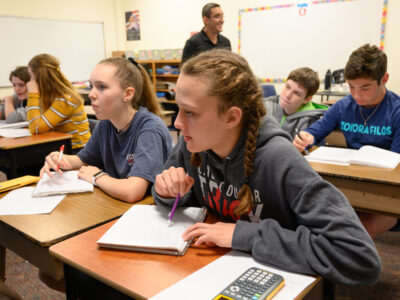 A group of middle school math students work together in the classroom.